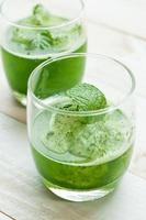 gröna smoothies på en brun bakgrund foto