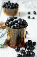 svarta vinbär i ett transparent glas foto