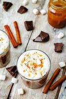 varm mörk choklad med vispad grädde, kanel och salt karamell foto