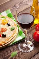 glas rött vin och italiensk pizza foto