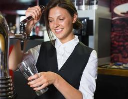 glad barmaid som drar en halvlök öl foto