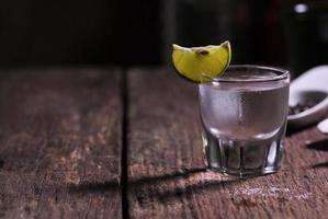 glas vodka skott med färsk kalk på träbord foto