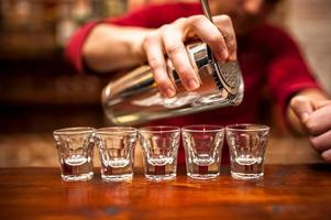 närbild av bartenderhand som häller alkoholhaltig dryck i nattklubb,