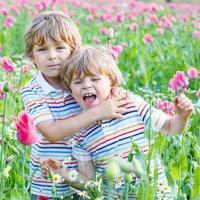 två glada små blonda barn i blommande vallmo-fält foto