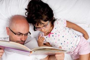 far och dotter som läser en bok i sängen