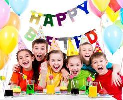 grupp skrattande barn som har kul på födelsedagsfesten. foto