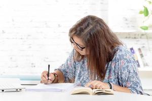 tonårsflicka som gör sina läxor foto