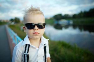 lilla herre med solglasögon utomhus foto