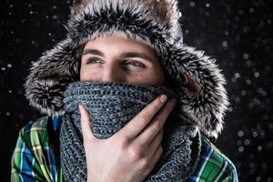 fundersam man i hatt och halsduk med snö foto