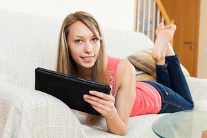 flicka på soffan med surfplattan foto