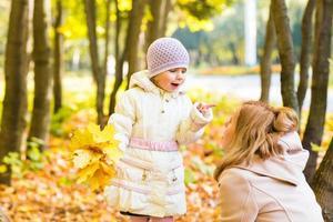 lycklig familj mor och lilla dotter spelar på höst promenad foto