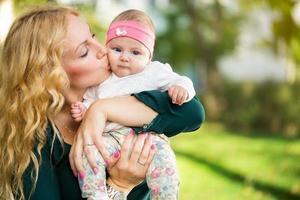 mamma kyssa baby i händerna foto