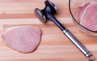 rå fläsksnitzel med köttbensmakare på träplatta foto