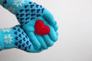 rött hjärta i händerna i varma handskar för alla hjärtans dag foto