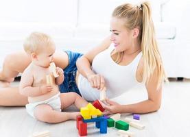 mamma och barn som leker med kvarter foto