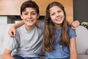porträtt av leende små syskon i vardagsrummet foto