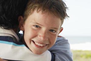 närbild av pojke som kramar far foto