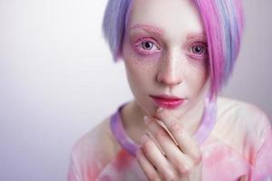 ung flicka med rosa ögon och hår, som en docka foto
