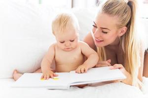 mamma läser bok med baby foto