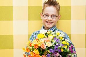 pojke som står med en bukett med färgglada blommor