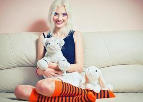 porträtt av söt blond tjej med kanin- och tigerleksaker foto