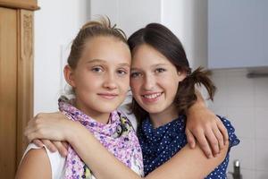 leende flickor som kramar i köket foto