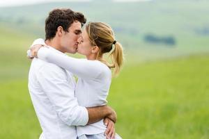 romantiska par som kysser på gräsmark foto