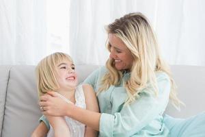 mamma som sitter i soffan med sin dotter foto