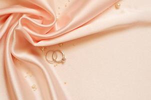 satängdraperi med pärlor och vigselringar foto