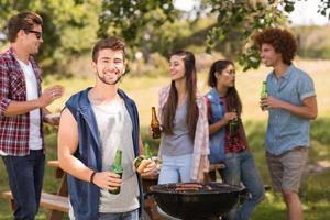 glada vänner i parken med grillfest foto