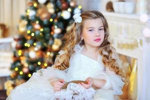 bedårande flicka vid julgranen foto