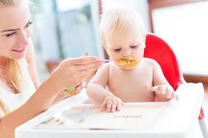 mamma som matar baby med sked foto