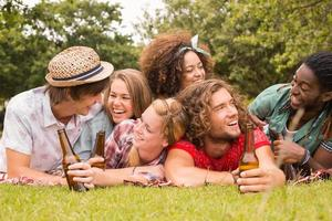 glada vänner i parken som har picknick foto