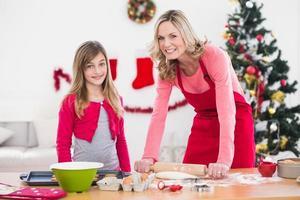 festlig mor och dotter som gör julkakor foto