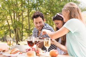 glada vänner i parken som äter lunch foto
