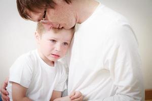 far tröstande son i tårar foto