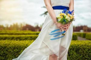 brudbukett med blommor i händerna på bruden