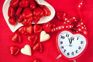 tid för söt kärlek. röd hjärtformad klocka med choklad foto