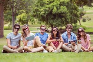 glada vänner i parken tittar på surfplattan foto
