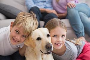 föräldrar tittar på barn på matta med labrador foto