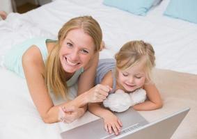 söt liten flicka och mamma på sängen med hjälp av bärbar dator foto