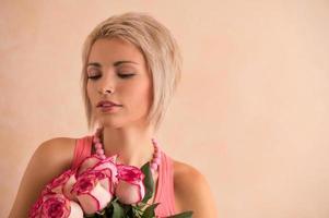 ung vacker kvinna med bukett med rosa rosor