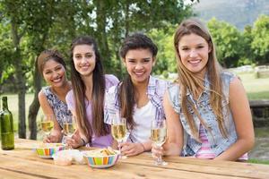 glada vänner i parken med vin foto