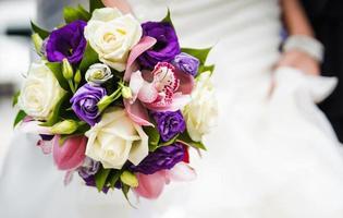 bröllop bukett med olika blommor i händerna på bruden foto