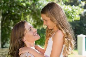 leende ung flicka och mamma på park foto