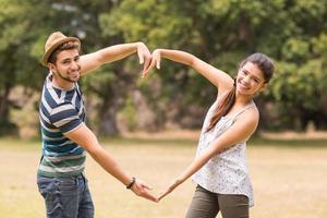 söta par i parken som gör hjärtaform foto