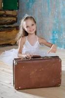 liten förtjusande ballerina i vit tutu med gamla vintage resväskor