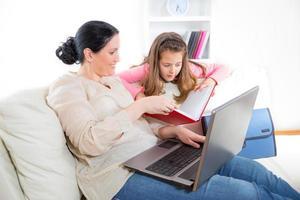 mamma och dotter som sitter på soffan och använder bärbar dator foto