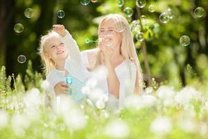glad mamma och dotter som blåser bubblor i parken foto