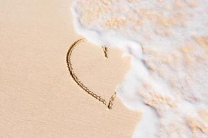 hjärta på sandstrand som tvättas bort foto